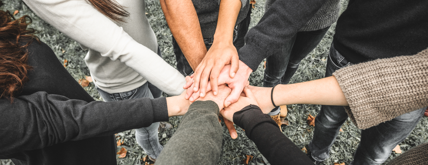 A group of people with their hands in the center.